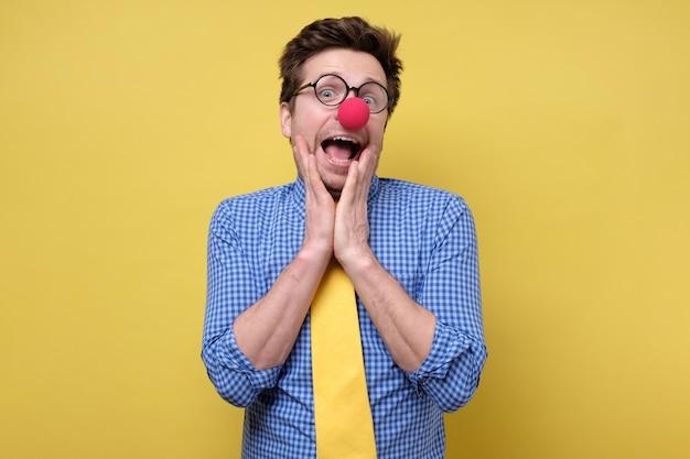 Homem com nariz de palhaço vermelho e gravata amarela sendo chocado. dia da mentira no dia primeiro de abril Foto Premium