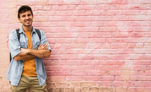 Homem com os braços cruzados com fundo rosa Foto gratuita