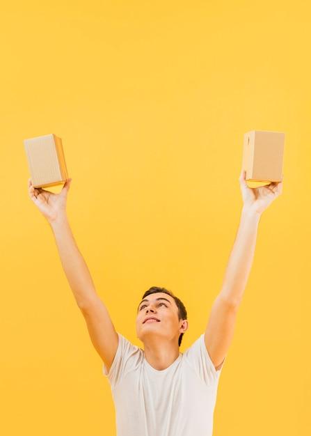 Homem com os braços levantados segurando pequenos pacotes Foto gratuita