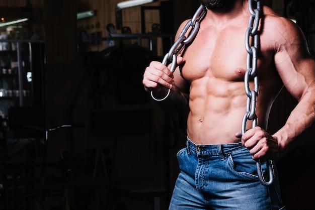 Homem com peito nu com corrente pesada Foto gratuita