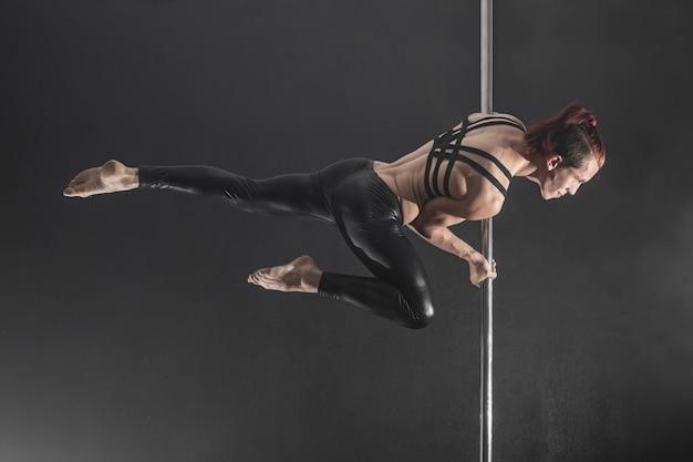 Homem com pilão. dançarina masculina dançando em um fundo preto Foto Premium
