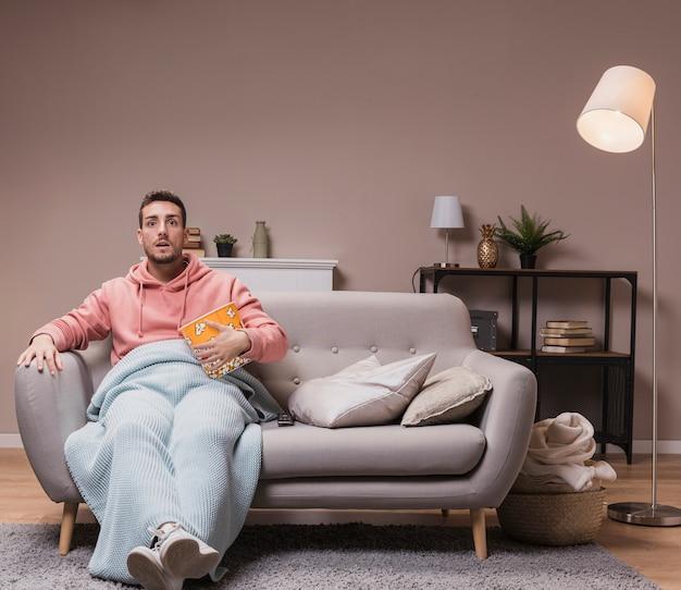 Homem com pipoca assistindo tv Foto gratuita