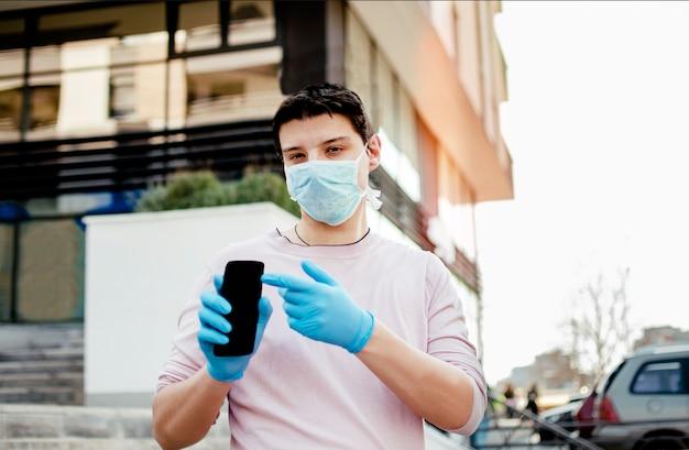 Homem com roupa médica protetora usando smartphone, andando na rua da cidade. Foto Premium