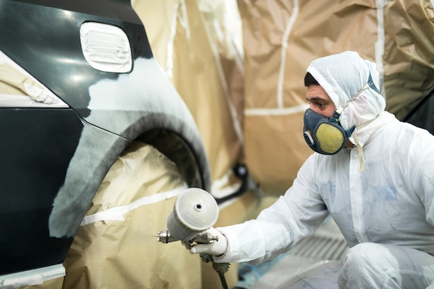 Homem com roupas de proteção e máscara pintando pára-choque de automóvel em oficina mecânica Foto gratuita