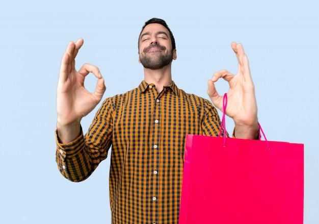 Homem com sacos de compras em zen posar em fundo azul isolado Foto Premium