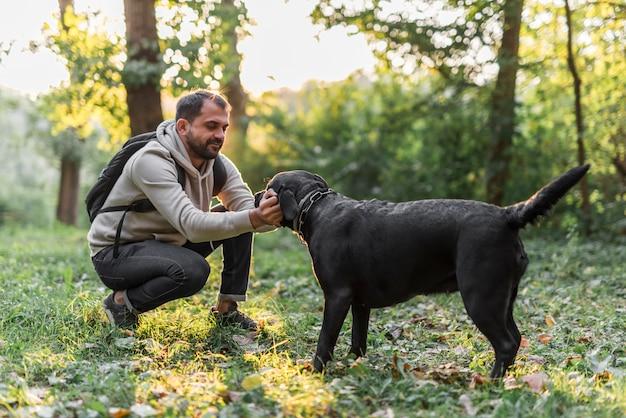 Homem, com, seu, pretas, labrador, tocando, em, jardim, ligado, grama verde Foto gratuita
