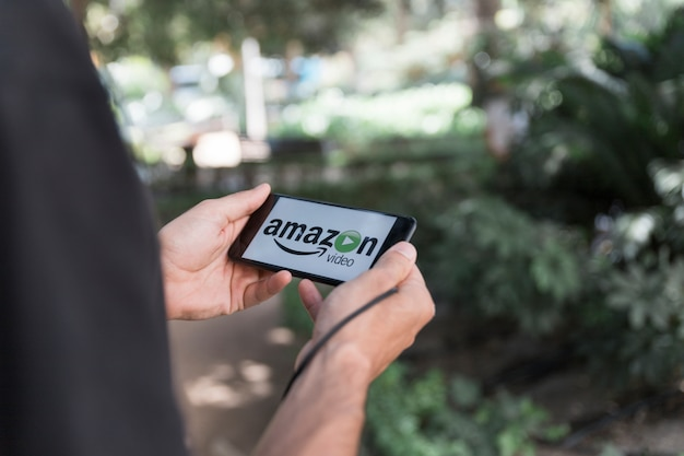 Homem, com, smartphone, mostrando, amazon, principal, vídeo, app Foto gratuita
