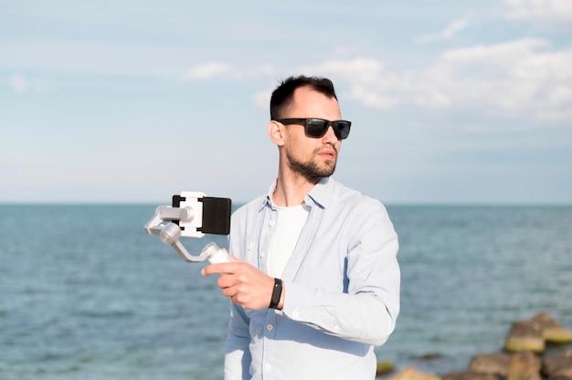 Homem com smartphone na beira-mar Foto gratuita