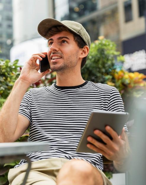 Homem com tablet na mão, falando ao telefone Foto gratuita