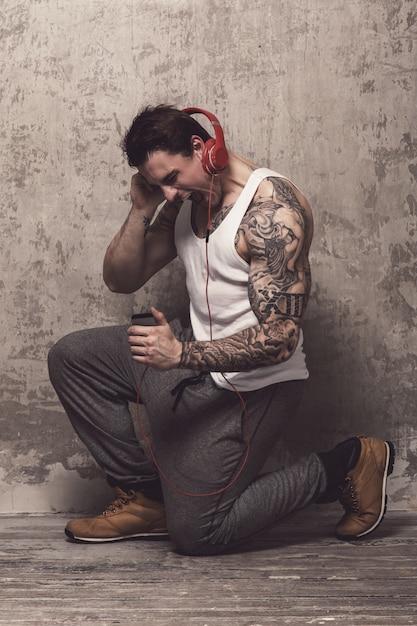 Homem com tatuagem, ouvindo música Foto gratuita