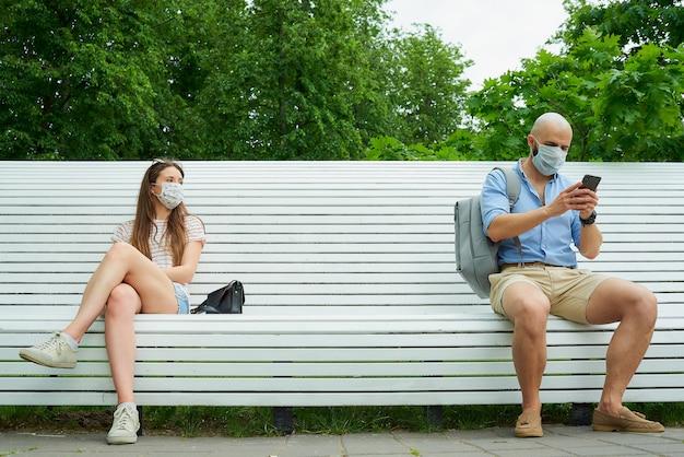 Homem com telefone e jovem sentada em extremos opostos de um banco, mantendo distância um do outro para evitar a propagação do coronavírus. Foto Premium
