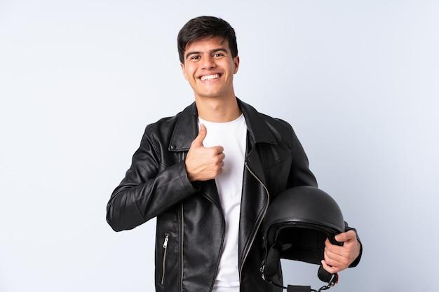 Homem com um capacete de moto sobre fundo azul isolado, dando um polegar para cima gesto Foto Premium