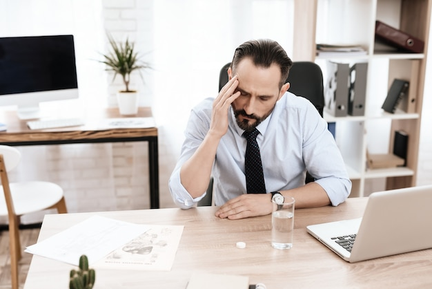 Homem com um copo está sentado à mesa e segurando a cabeça dele. Foto Premium