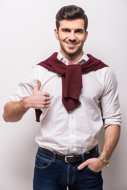 Homem com um lenço no pescoço, mostrando os polegares. Foto Premium
