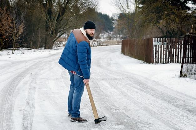 Homem com um machado andando em uma estrada de neve Foto Premium