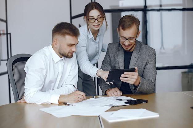 Homem com um tablet. parceiros de negócios em uma reunião de negócios. pessoas sentadas à mesa Foto gratuita