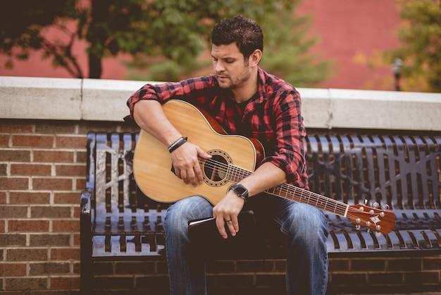 Homem com um violão e um livro sentado em um banco do parque Foto gratuita