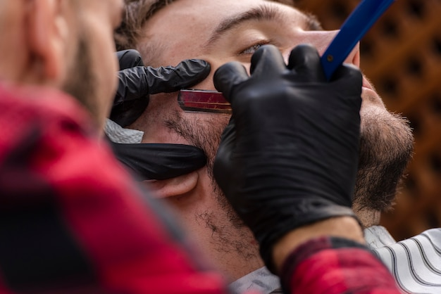 Homem com uma barba aparada com uma lâmina Foto gratuita