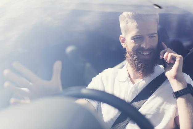 Homem com uma barba senta-se ao volante de um veículo elétrico Foto Premium