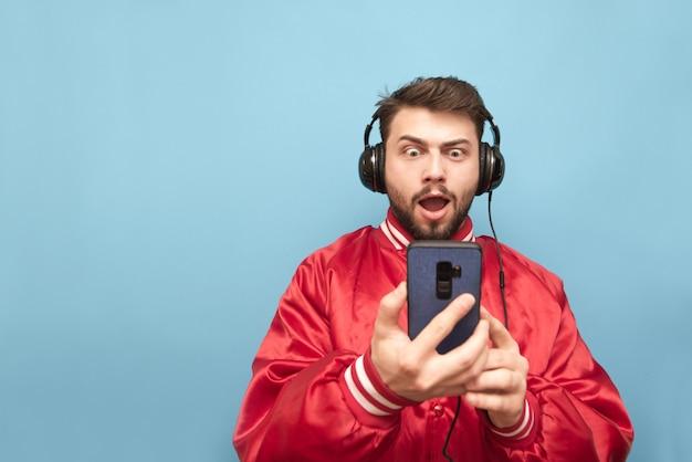 Homem com uma jaqueta vermelha e barba fica azul com fones de ouvido e um smartphone nas mãos Foto Premium