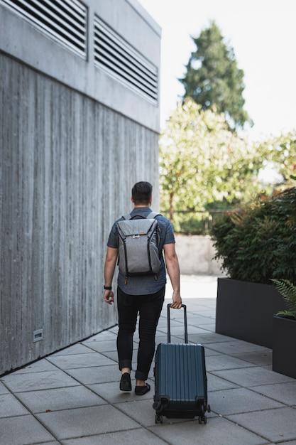 Homem com uma mochila, levando uma mala Foto gratuita