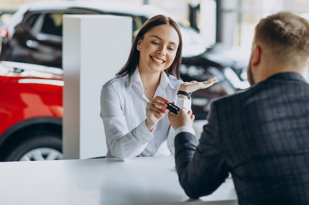 Homem com vendedora em showroom de carros Foto gratuita