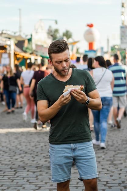 Homem comendo comida de rua. hotdogs de rua Foto gratuita