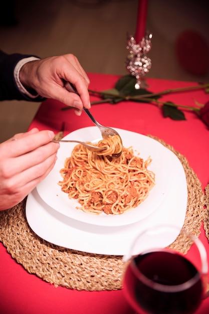 Homem comendo macarrão na mesa festiva Foto gratuita