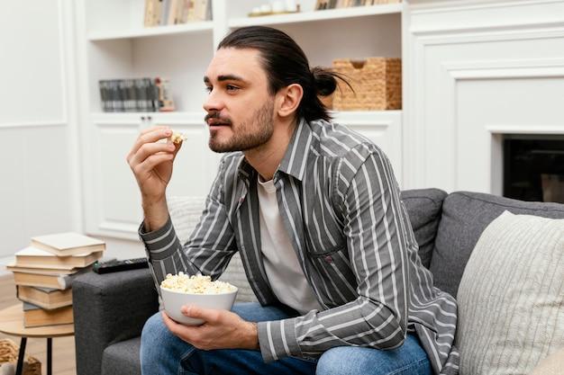 Homem comendo pipoca e assistindo tv no sofá Foto gratuita
