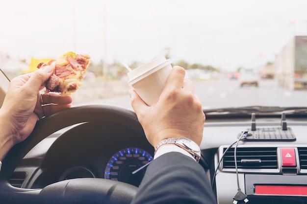 Homem, comer, pizza, e, café, enquanto, dirigindo carro, perigosamente Foto gratuita