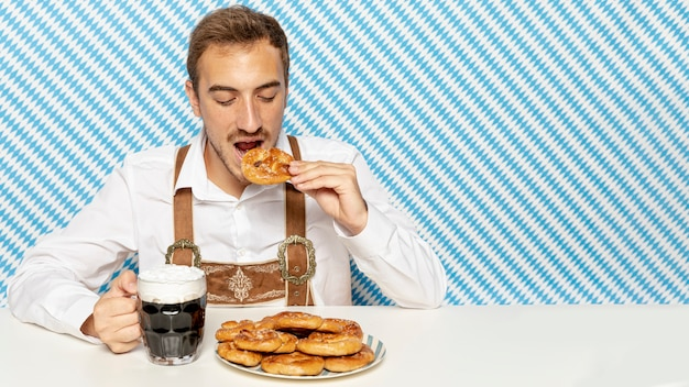 Homem, comer, pretzels, com, pretas, cerveja Foto gratuita