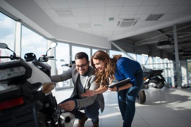 Homem comprando motocicleta veloz com ajuda de linda vendedora morena Foto gratuita