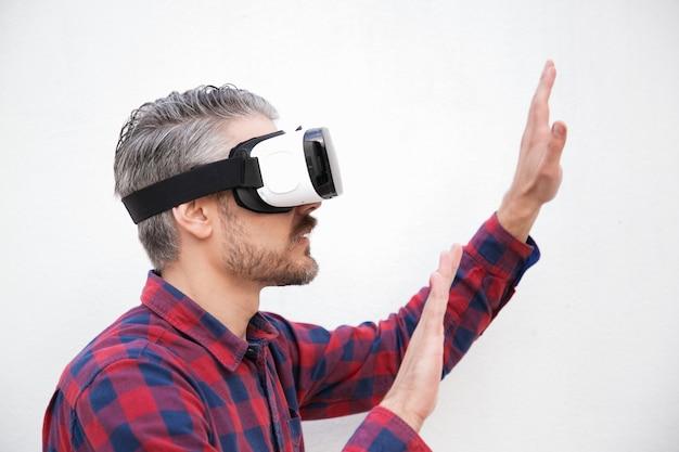 Homem concentrado no fone de ouvido vr movendo as mãos Foto gratuita