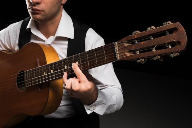 Homem concentrado tocando notas na guitarra Foto gratuita