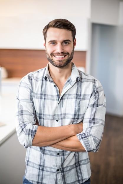 Homem confiante com os braços cruzados pelo balcão da cozinha Foto Premium