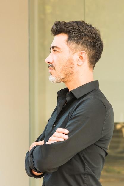 Homem confiante na camisa preta com os braços cruzados, olhando para longe Foto gratuita