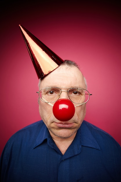 Homem confuso com nariz de palhaço vermelho e chapéu de aniversário Foto gratuita