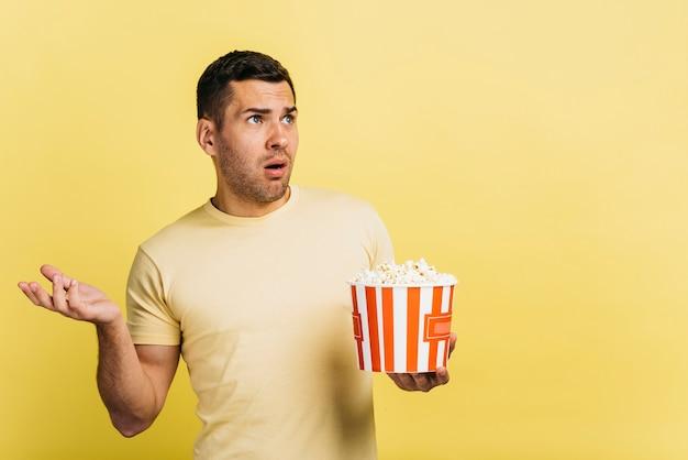 Homem confuso comendo pipoca com espaço de cópia Foto gratuita