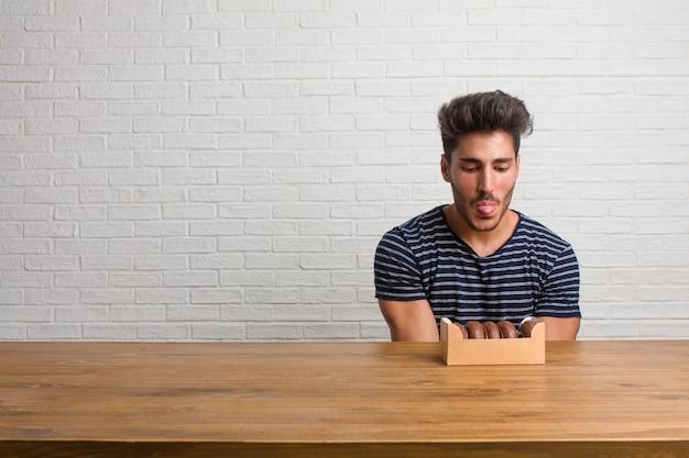Homem considerável e natural novo que senta-se em uma expressão da tabela da confiança e da emoção, do divertimento e amigável, mostrando a língua como um sinal do jogo ou do divertimento. comendo rosquinhas de chocolate. Foto Premium