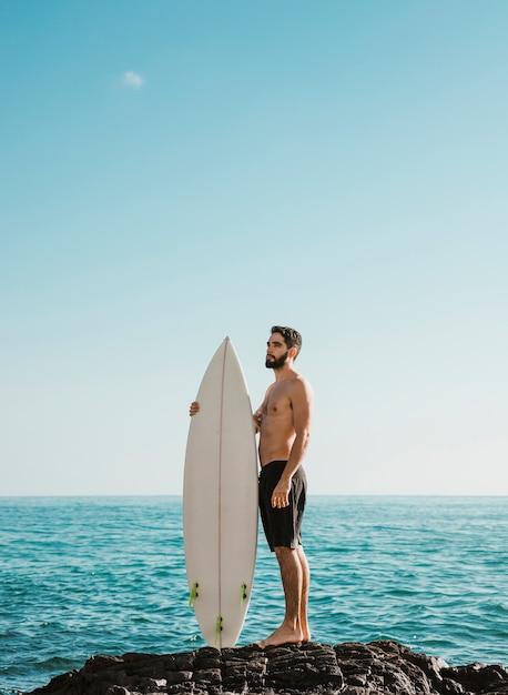 Homem considerável novo com placa de ressaca na pedra perto do mar Foto gratuita