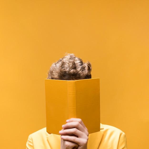 Homem considerável novo que lê um livro em uma cena amarela Foto gratuita