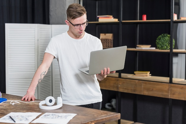 Homem considerável novo que olha o portátil à disposição Foto gratuita