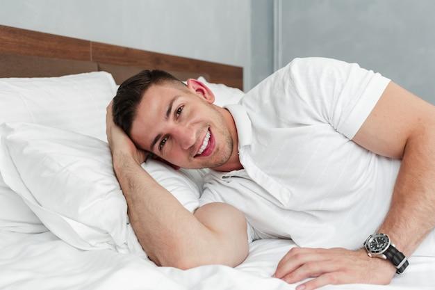 Homem considerável novo que relaxa na cama após um dia difícil no trabalho Foto Premium