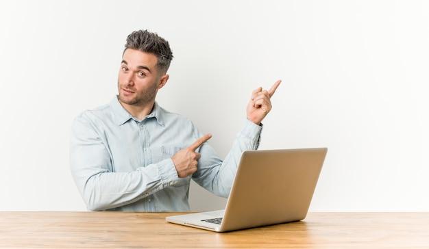 Homem considerável novo que trabalha com seu portátil que sorri alegremente apontando com dedo indicador afastado. Foto Premium