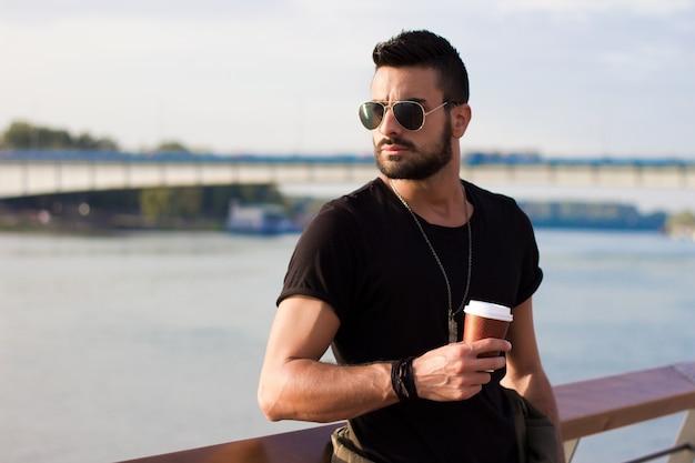 Homem considerável que bebe ao ar livre o café. Com óculos de sol, um cara com barba. Efeito Instagram. Foto gratuita