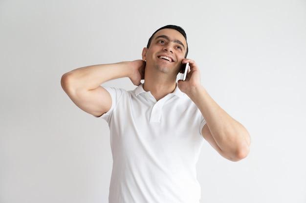 Homem considerável relaxado que fala no telefone móvel. indivíduo novo de sorriso que chama o smartphone. Foto gratuita