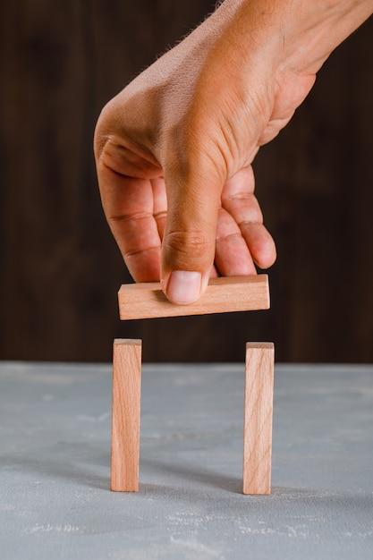 Homem construindo arco de blocos de madeira. Foto gratuita