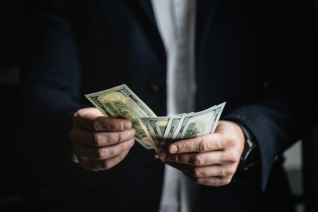 Homem contando dinheiro, homem com roupas de negócios com dólares. Foto Premium