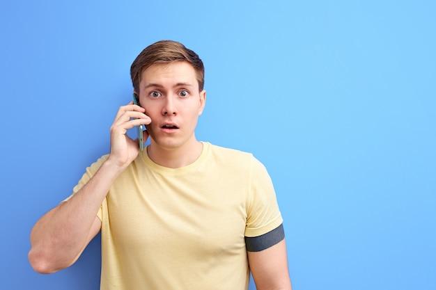 Homem conversando ao telefone, conversando com alguém e compartilhando notícias, fica em estado de choque enquanto ouve uma conversa. fundo azul isolado Foto Premium