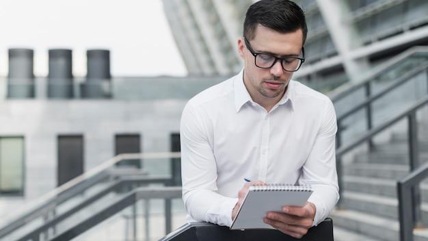 Homem corporativo, escrevendo no bloco de notas Foto gratuita
